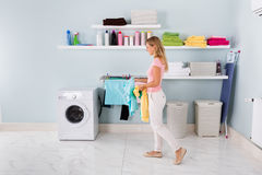 Woman Walking With Clothes In Utility Room. Happy Woman Washing Stained Clothes In Washing Machine In Utility Room royalty free stock photo