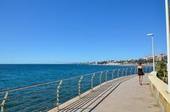 Woman walking at the coastal promenade Stock Photos