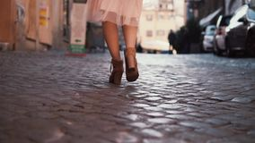 Woman walking on cobblestone pavement road. Girl exploring new city wearing in shoes and skirt. Close-up view. Young stylish woman walking on cobblestone stock video footage