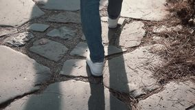 Woman walking on cobblestone pavement road, old way. Girl exploring new city wearing in sneakers. Close-up view. Young stylish woman walking on cobblestone stock video footage