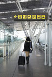 Woman walking through a corridor of an airport Stock Image