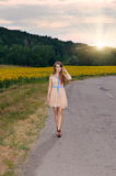 Woman walking by country road Stock Image