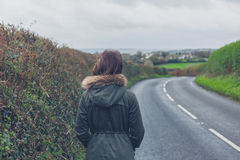 Woman walking on country road Stock Photos