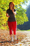 Woman walking cross country trail in autumn forest Royalty Free Stock Photos