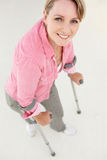 Woman walking with crutches. Smiling Stock Image