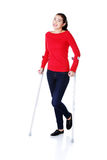Woman walking with crutches Royalty Free Stock Photography