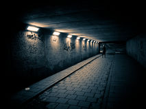 Woman walking in a dark tunnel Stock Images
