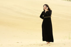 Woman walking by desert calling on cellphone Royalty Free Stock Photos