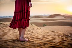 Woman walking in the desert. At sunset stock photo