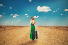 Woman walking through desert talking on phone carrying suitcase Stock Photo