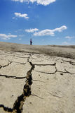 Woman walking on desolate cracked earth landscape Stock Image