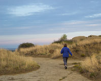 Woman walking on dirt path amid sandstone rocks and dried grass Royalty Free Stock Photo