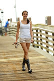 Woman walking on the dock with a fishing pole Royalty Free Stock Images