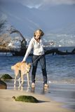 Woman walking dog. Royalty Free Stock Image