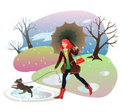 Woman walking a dog in the autumn park. Woman with umbrella walking a dog among the puddles in the autumn park. It's raining Stock Photo