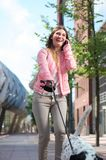 Woman walking dog and calling by phone outdoors Royalty Free Stock Photography