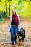 Woman walking the dog on leash in park Royalty Free Stock Images