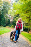 Woman walking the dog on leash in park Stock Photos