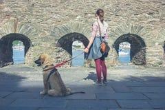 Woman walking dog near stone walls Royalty Free Stock Photo