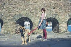 Woman walking dog near stone walls Stock Photo
