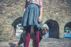 Woman walking dog near stone walls Stock Photography