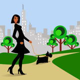 Woman walking Dog in Park. Afro-American woman walking Scottish Terrier dog in park Stock Photography