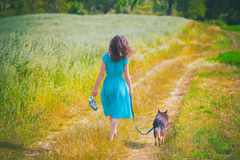 Woman walking with dog. Young woman walking barefoot with dog in the field Royalty Free Stock Photo