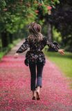 Woman walking down barefoot at alley with blossom trees royalty free stock images