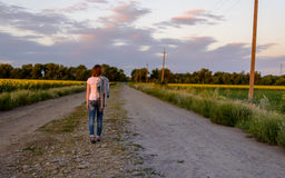 Woman walking down a country road Stock Image