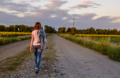 Woman walking down a country road Stock Photo