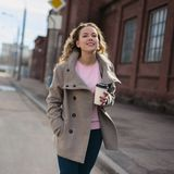 Woman walking down and drinking coffee Stock Photos