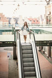 Woman walking down the escalator at shopping mall Stock Image