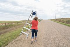 Woman walking down a rural road with a step ladder Royalty Free Stock Photos