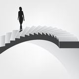 Woman walking down on spiral staircase Royalty Free Stock Image