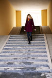 Woman walking down stairs Stock Image