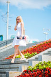 Woman  walking down stairs outdoors. Beautiful young blond woman in a white dress walking down stairs outdoors Stock Photo