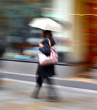 Woman walking down the street on a rainy day Royalty Free Stock Images