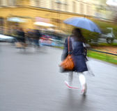 Woman walking down the street on a rainy day Royalty Free Stock Image