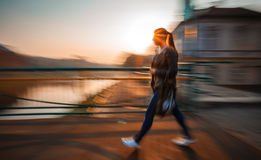 Woman Walking Down The Street In Morning Sun Light Stock Image
