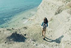 Woman walking down to the sea Stock Image