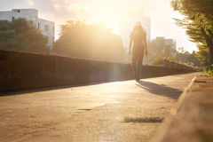 Woman walking exercise on the road in the park, sunset backgroun. D Stock Image