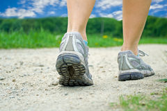 Woman on walking exercise in summer. Woman walking on dirt road in summer Royalty Free Stock Images