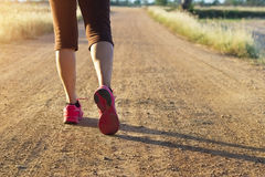 Woman walking exercise on trail in summer nature. Woman walking exercise on trail dirt road in summer nature Stock Images