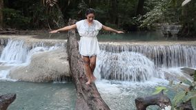 Woman walking on a fallen tree over water. Young woman walking on a fallen tree over water stock video