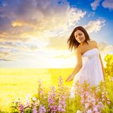 Woman walking in a field at sunset. Beautiful brunette woman walking in a field at sunset and touching flowers Stock Photo