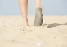 Woman walking with flip flops on beach. Low angle from behind view of woman walking with flip flops on beach Royalty Free Stock Photo