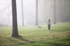 Woman walking in foggy forest Stock Images