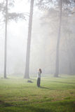 Woman walking in foggy forest Royalty Free Stock Photography
