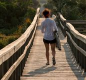 Woman walking on footbridge Stock Photography