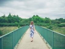 Woman walking on footbridge in country Stock Photos